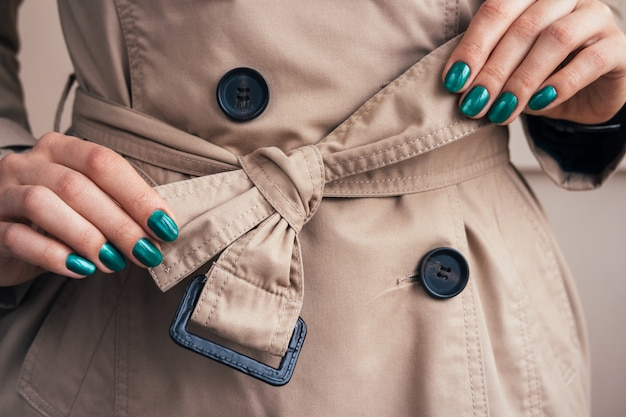 Female hands with a bright manicure tie belt on a coat