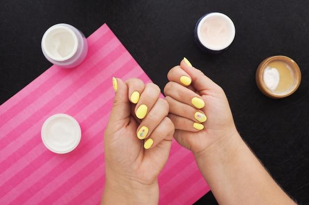 Женские руки с ярко-желтым маникюром. на черном столе баночки с кремом, лаком и розовая салфетка.