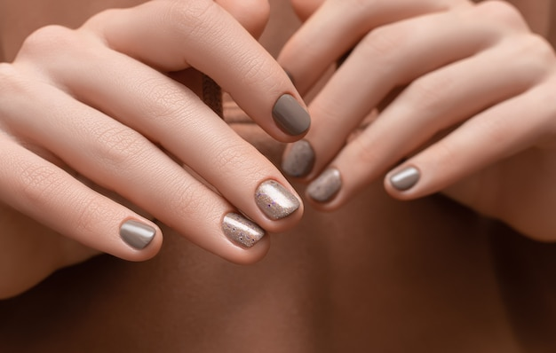 Female hands with brown nail design on brown fabric surface.