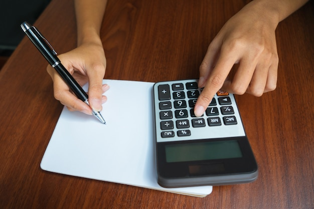 Female hands with calculator writing in notebook