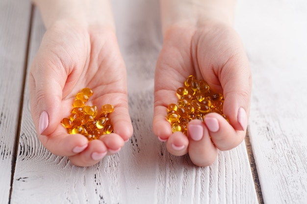 Female hands with capsules of fish oil and vitamin e