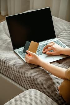 カード空白のモックアップディスプレイラップトップを持つ女性の手女性の買い物客は、アプリのwebバンキング用の自宅のラップトップディスプレイモックアップでソファに座っている間、ラップトップとクレジットデビットカードを使用してオンライン購入を行います