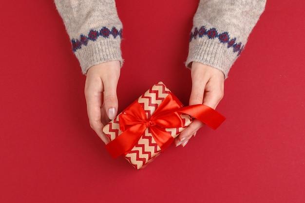 Женские руки с рождественским подарком на красном фоне вид сверху копией пространства