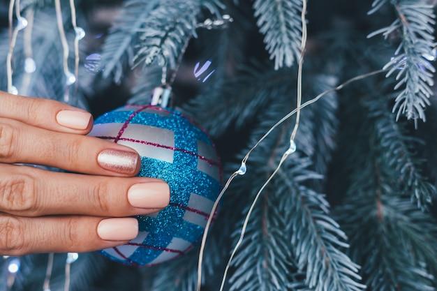 크리스마스 새 해 네일 디자인 여성 손. 누드 베이지 매니큐어 매니큐어, 한 손가락으로 반짝이는 황금색 청동