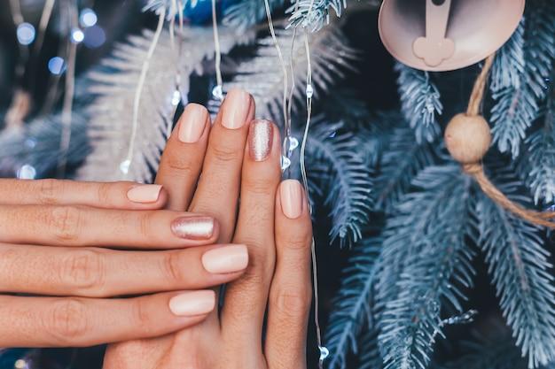 Женские руки с дизайном ногтей рождество новый год. маникюр с лаком для ногтей телесного бежевого цвета, блестящая золотистая бронза на один палец