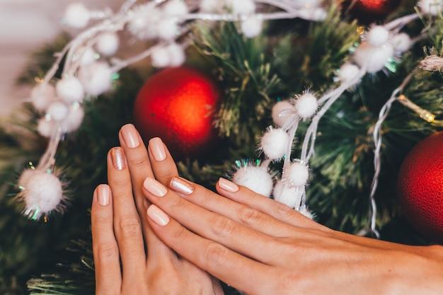 Mani femminili con unghie di natale capodanno. manicure con smalto beige nudo