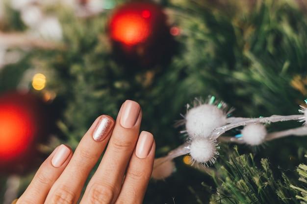 Женские руки с дизайном ногтей рождество новый год. нюдовый бежевый маникюр с лаком
