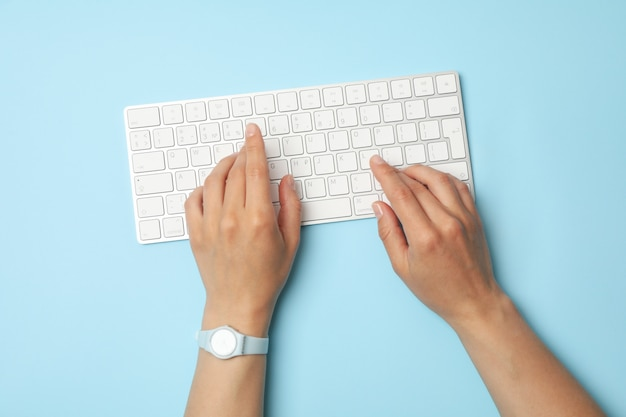 Female hands with clock are typing on the keyboard on blue