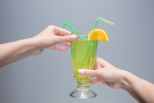 The female hands with cocktail on gray space