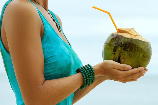 Female hands with a coconut drink