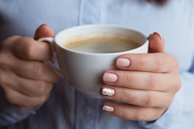 コーヒードリンクと女性の手