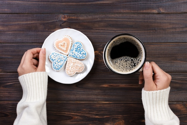 Female hands with coffee and heart shaped cookies on wooden table, top view