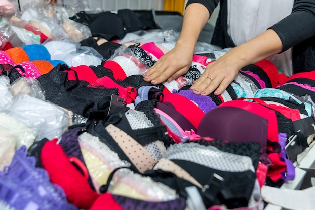 Female hands with colorful bras in underwear shop