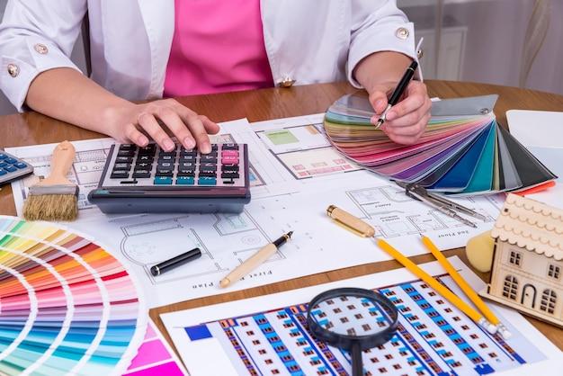 Женские руки с образцом цвета и калькулятором
