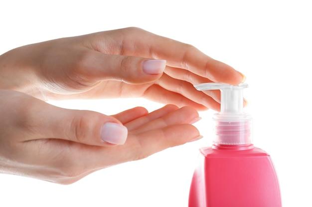 Женские руки с кремом на белом