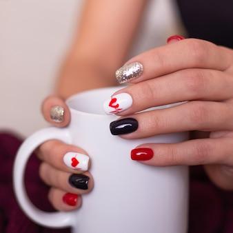 Женские руки с креативным маникюрным дизайном ногтей в форме сердца