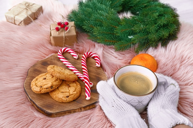 柔らかい格子縞にコーヒー、クッキー、クリスマスの装飾を施した女性の手