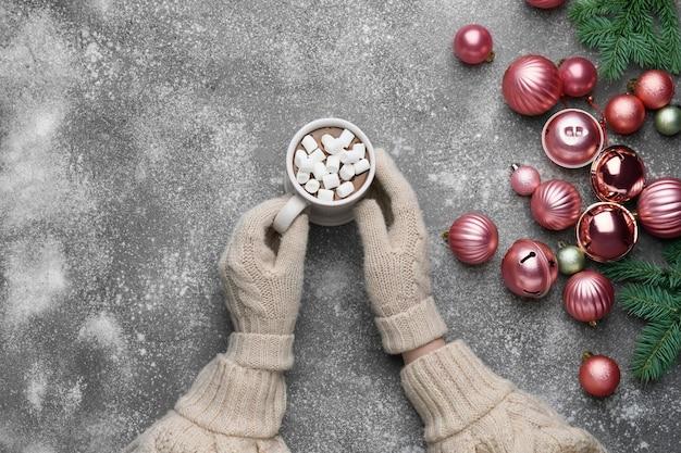 灰色のホットチョコレートとクリスマスボールのカップを持つ女性の手