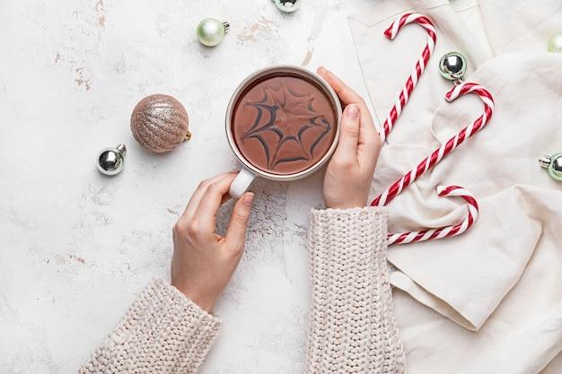 分離されたホットチョコレートのカップを持つ女性の手