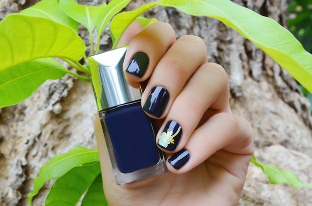 暗い青色のネイルデザインと女性の手。