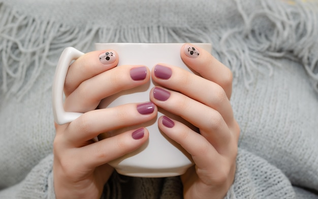 Female hands with dark pink nail design