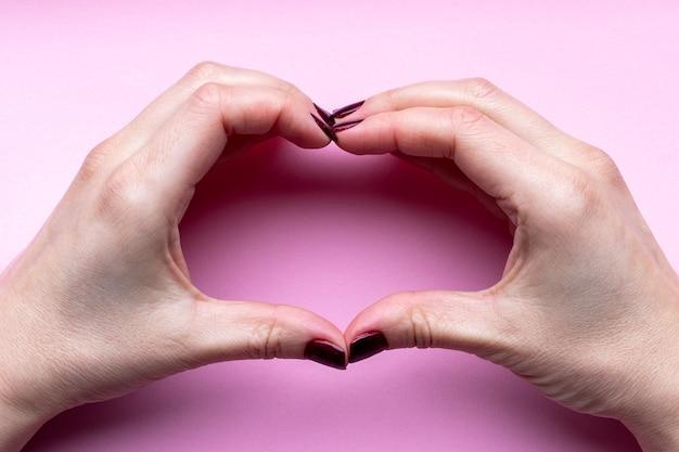 Женские руки с темно-красными блестящими ногтями, делающими символ сердца на розовом фоне
