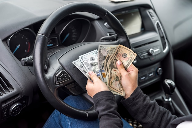 Female hands with dollar banknotes closeup on steering wheel