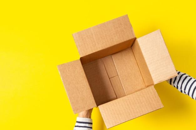 Женские руки с пустой открытой картонной коробкой на желтом фоне
