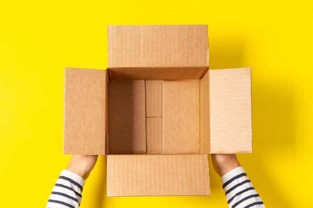Женские руки с пустой открытой картонной коробкой