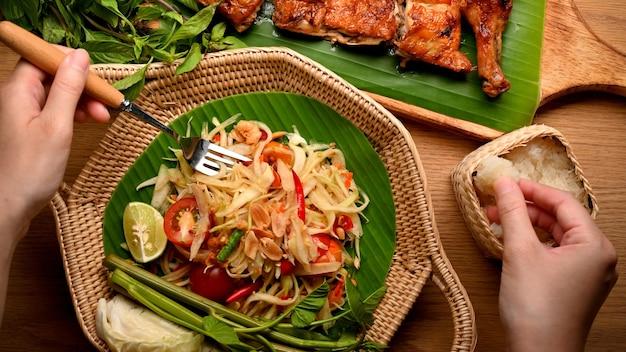パパイヤサラダソムタムとタイ風グリルチキンの上面図を食べるフォークともち米の女性の手