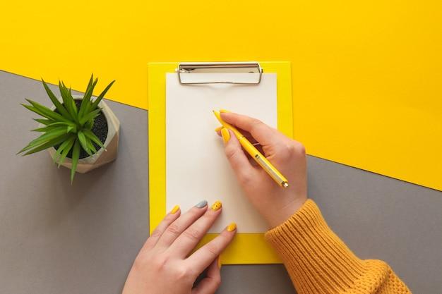 紙に新鮮なマニキュアを書いている女性の手オフィスのテーブルデスクトレンディな黄色と灰色