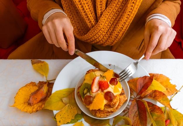 Женские руки с фруктовым пирогом на фоне осенних листьев