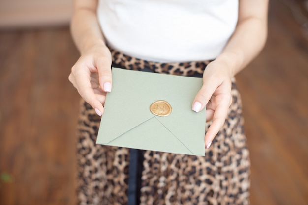 Female hands with a gentle manicure in bright colors holding an invitation to the envelope for a wedding graduation greeting card on a beige background with a wax seal