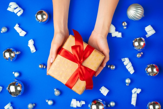 Female hands with gift box on a blue background