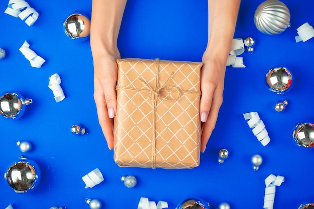 Female hands with gift box on a blue