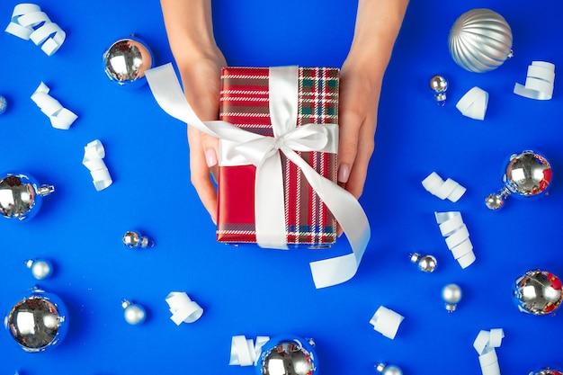 Женские руки с подарочной коробкой на синем фоне