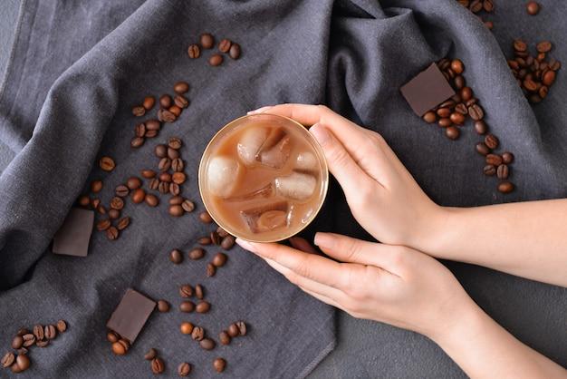おいしいアイス コーヒーのグラスを持つ女性の手