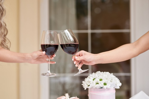 Female hands with glasses of red wine
