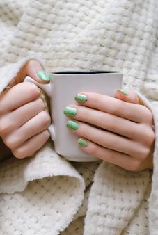 キラキラグリーンネイルデザインと女性の手。
