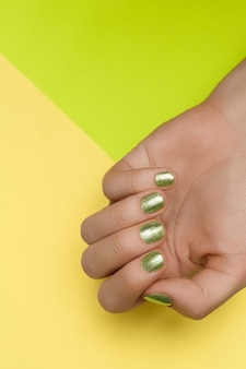 Female hands with green nail design. green nail polish manicured hands. female hands on green background