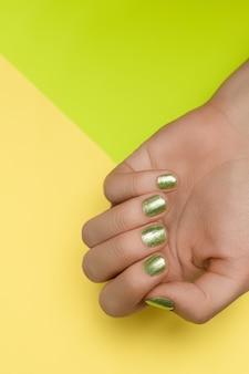 緑のネイルデザインの女性の手。緑のマニキュアの手入れの行き届いた手。緑の背景に女性の手