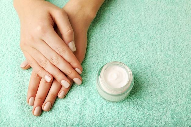 Женские руки с банкой крема на поверхности ткани