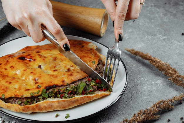 Female hands with a knife and a fork cut khachapuri with lamb and chili. georgian national food.