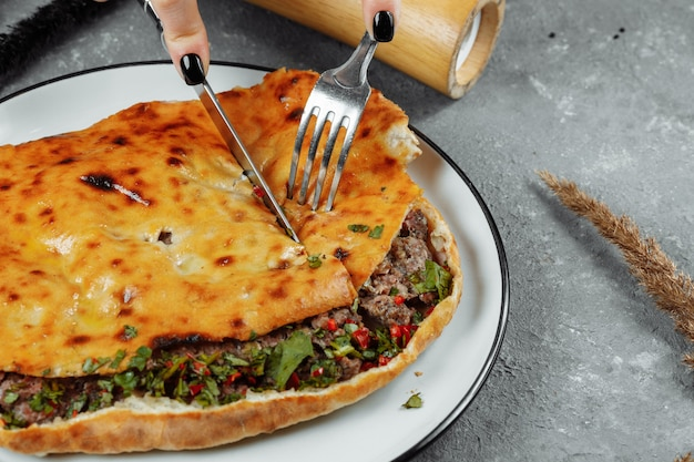 Female hands with a knife and a fork cut khachapuri with lamb and chili