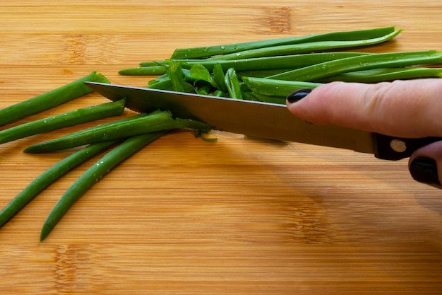 Female hands with a knife, slicing vegetables on a wooden board on a white background. woman cuts green onions