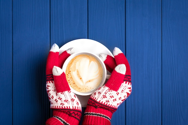 Female hands with knitted gloves with new year's pattern hold white cup with hot coffee cappuccino on blue wooden