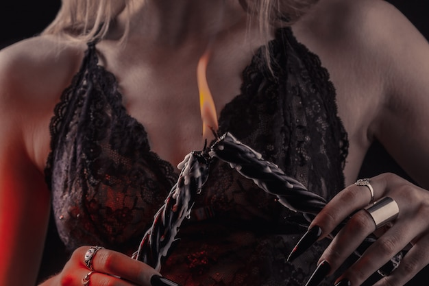 Female hands with long nails hold burning candles, witchcraft on halloween.