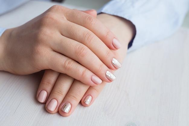 マニキュアとピンクの磨かれた爪を持つ女性の手