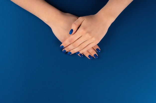 Female hands with manicure of classic blue color on blue background. close up