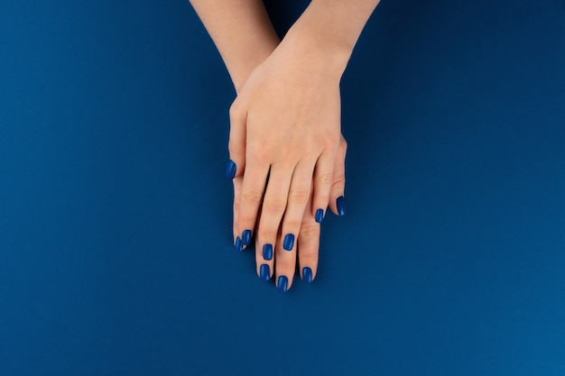 Female hands with manicure of classic blue color